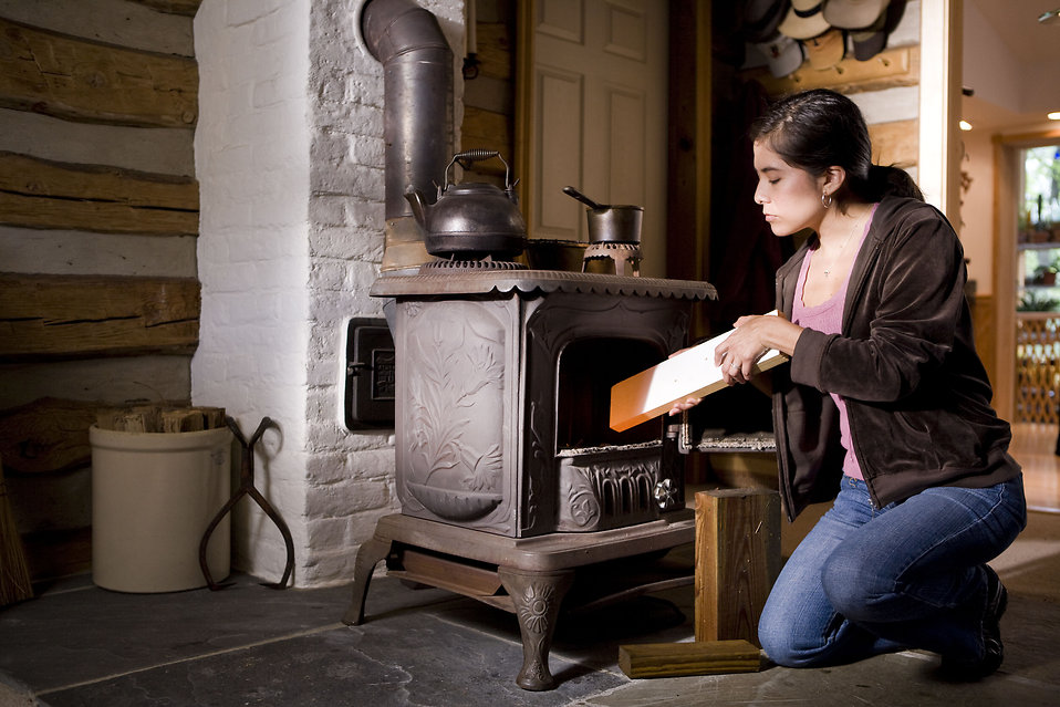 16950-a-woman-placing-wood-into-a-stove-pv
